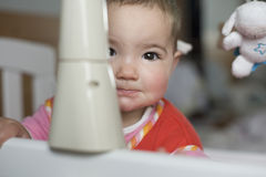 Baby girl playing hide-and-go-seek Royalty Free Stock Image