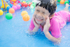 Baby girl playing in kiddie pool. A baby girl in pink suit playing water and balls in blue kiddie pool Royalty Free Stock Images