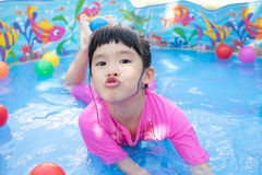 Baby girl playing in kiddie pool. A baby girl in pink suit playing water and balls in blue kiddie pool Stock Photos