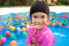 Baby girl playing in kiddie pool. A baby girl in pink suit playing water and balls in blue kiddie pool Royalty Free Stock Photos