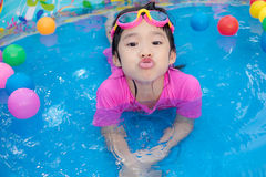 Baby girl playing in kiddie pool. A baby girl in pink suit playing water and balls in blue kiddie pool Stock Image