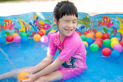 Baby girl playing in kiddie pool Royalty Free Stock Image
