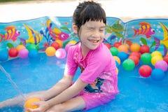Baby girl playing in kiddie pool Royalty Free Stock Image