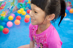 Baby girl playing in kiddie pool Stock Images