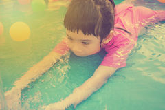 Baby girl playing in kiddie pool - vintage effect. A baby girl in pink suit playing water and balls in blue kiddie pool - vintage effect Royalty Free Stock Photography