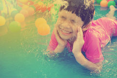 Baby girl playing in kiddie pool - vintage effect. A baby girl in pink suit playing water and balls in blue kiddie pool - vintage effect Stock Photography