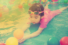 Baby girl playing in kiddie pool - vintage effect. A baby girl in pink suit playing water and balls in blue kiddie pool - vintage effect Stock Photos