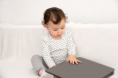 Baby girl playing with a laptop Stock Images
