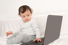 Baby girl playing with a laptop Stock Image