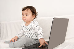 Baby girl playing with a laptop Royalty Free Stock Photo