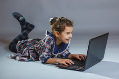 Baby girl playing laptop on gray background Royalty Free Stock Photography