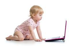 Baby girl playing at laptop Stock Photos
