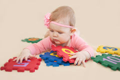 Baby girl playing with numbers Stock Photos