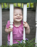 Baby girl playing outdoors. Happy baby girl outdoors looking through wooden posts of gazebo stock photo