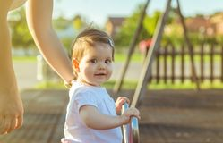 Baby girl playing over a seesaw swing on the park Stock Photos