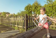 Baby girl playing over a seesaw swing on the park Stock Image