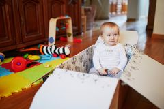 Baby girl playing with paper box in nursery royalty free stock photography