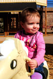 Baby Girl Playing at Park. A baby girl riding a horse at the park Stock Image
