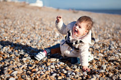Baby girl playing in the pebbles on the beach Stock Photos