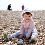 Baby girl playing with pebbles on the beach Stock Photography