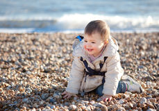 Baby girl playing in the pebbles on the beach Stock Images