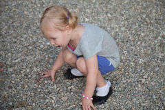 Baby girl playing with pebbles on the park Stock Photography