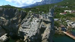 Baby girl playing with pebblesAerial view of castle Swallow's Nest on the rock in Crimea stock footage