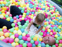 Baby girl playing in a pool of balls Stock Photos