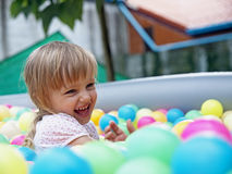 Baby girl playing in a pool of balls Royalty Free Stock Image