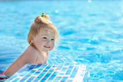 Baby girl playing in pool Stock Photos