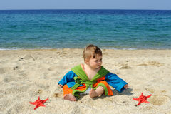 Baby girl playing with red sea stars on the beach Royalty Free Stock Photography