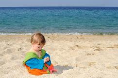 Baby girl playing with red sea stars on the beach Royalty Free Stock Photos