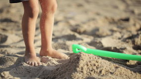 Baby girl playing with red toy bucket and shovel on the sandy beach stock footage