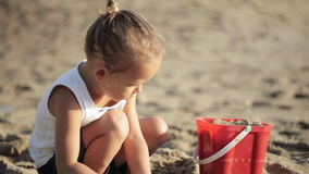Baby girl playing with red toy bucket and shovel on the sandy beach stock video footage