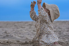 Baby girl playing with sand on the beach. Cute toddler playing with sand on the beach Stock Photo