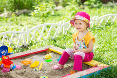 Baby girl playing in a sandbox Royalty Free Stock Image