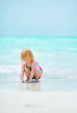 Baby girl playing on sea coast Royalty Free Stock Images