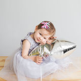 baby girl playing with silver star-shaped balloon. Stock Image