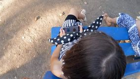 Baby girl playing smartphone. Toddler girl is playing a smartphone outdoors. Above view stock footage
