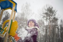 baby girl playing snowballs in winter Park stock photography