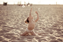 Baby girl playing with soap bubbles on the beach Royalty Free Stock Image
