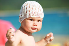 Baby girl playing with stones on the beach Royalty Free Stock Photos