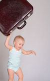 Baby girl playing with suitcase on grey background Stock Photos