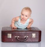 Baby girl playing with suitcase on grey background Royalty Free Stock Photo