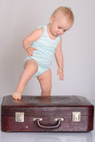 Baby girl playing with suitcase on grey background Royalty Free Stock Photography