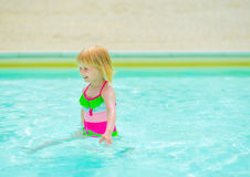 Baby girl playing in swimming pool. Happy baby girl playing in swimming pool royalty free stock photography
