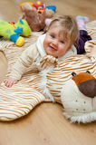Baby girl playing on tiger rug. Cute baby girl playing on soft tiger rug with teddy bear toys royalty free stock photo