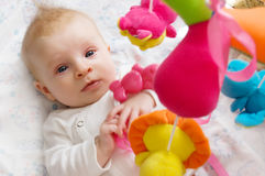 Baby girl playing with toys stock photos