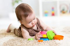 Baby girl playing with toys indoor Stock Image