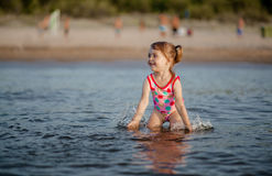 Baby girl playing with a water in the sea Royalty Free Stock Photos